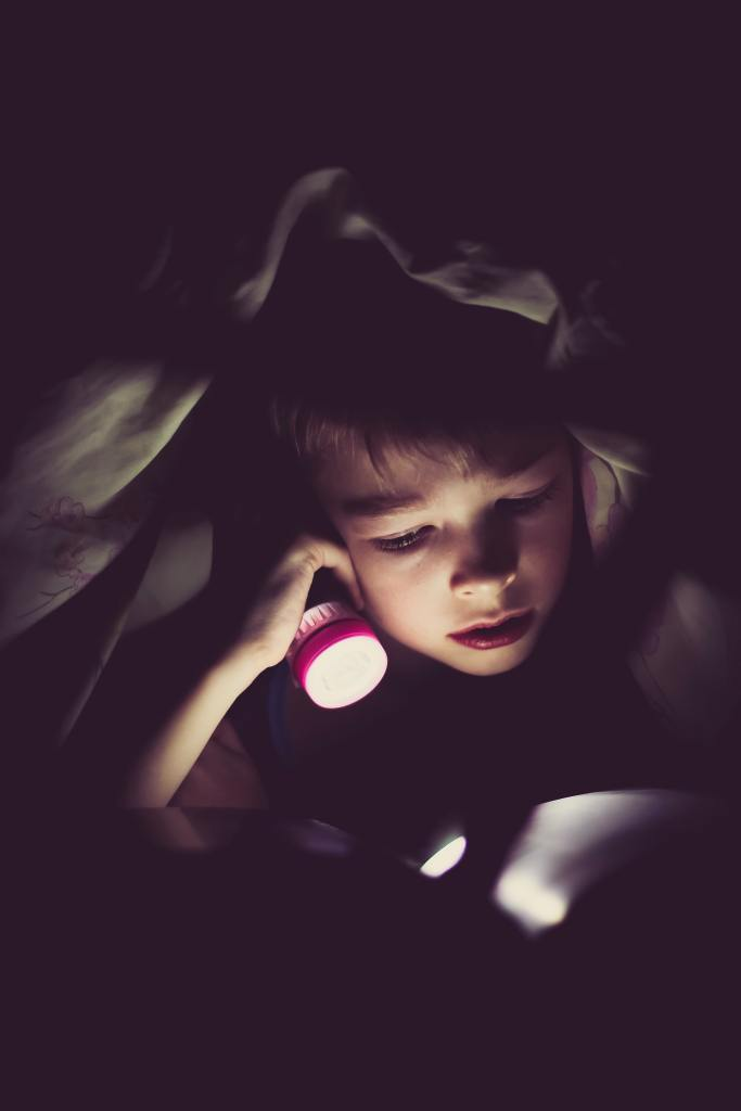 A child reading a book at bedtime
