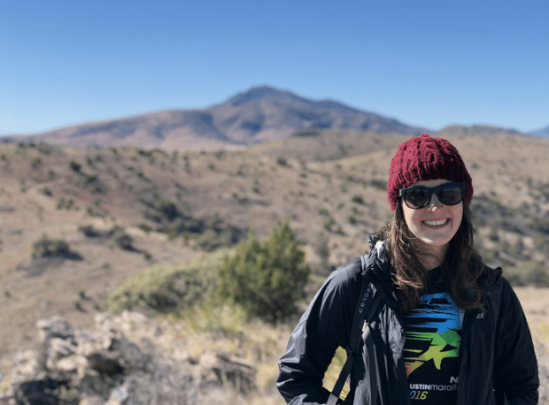 the blog writer Emmalee Calvert in hiking gear in front of West Texas mountains