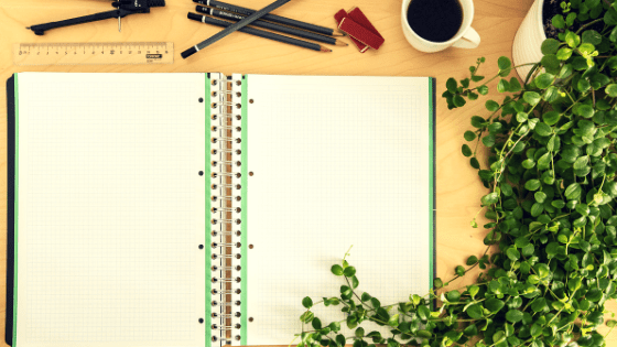 a desk filled with a green fern, a notebook, ruler, pencils, erasers, and a cup of coffee, all waiting for someone to sit and prepare to succeed on their test