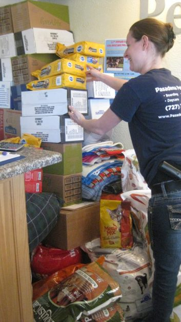 Sarah Davis, an employee at the Pasadena Pet Motel, stacks some of the many bags of pet supplies that had already been donated for Get Rescued two weeks before the event.