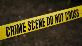 "A yellow tape reading ""Crime Scene Do Not Cross"""