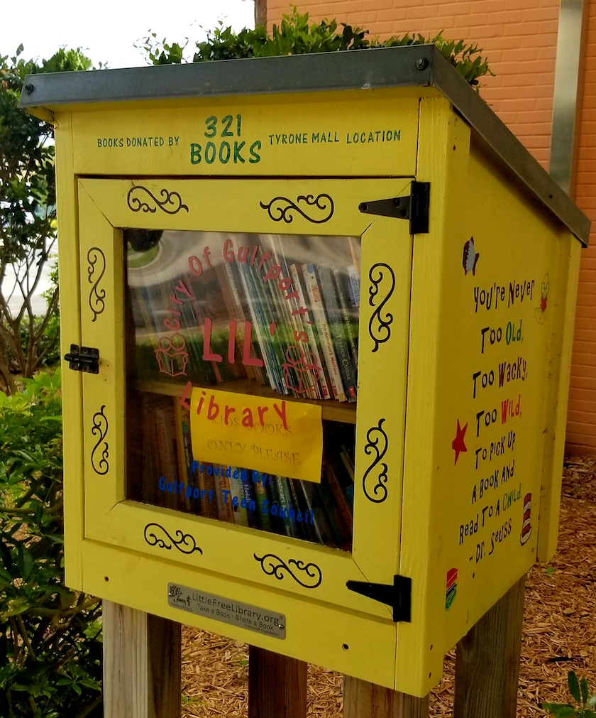 A yellow little free library box with designs and writing