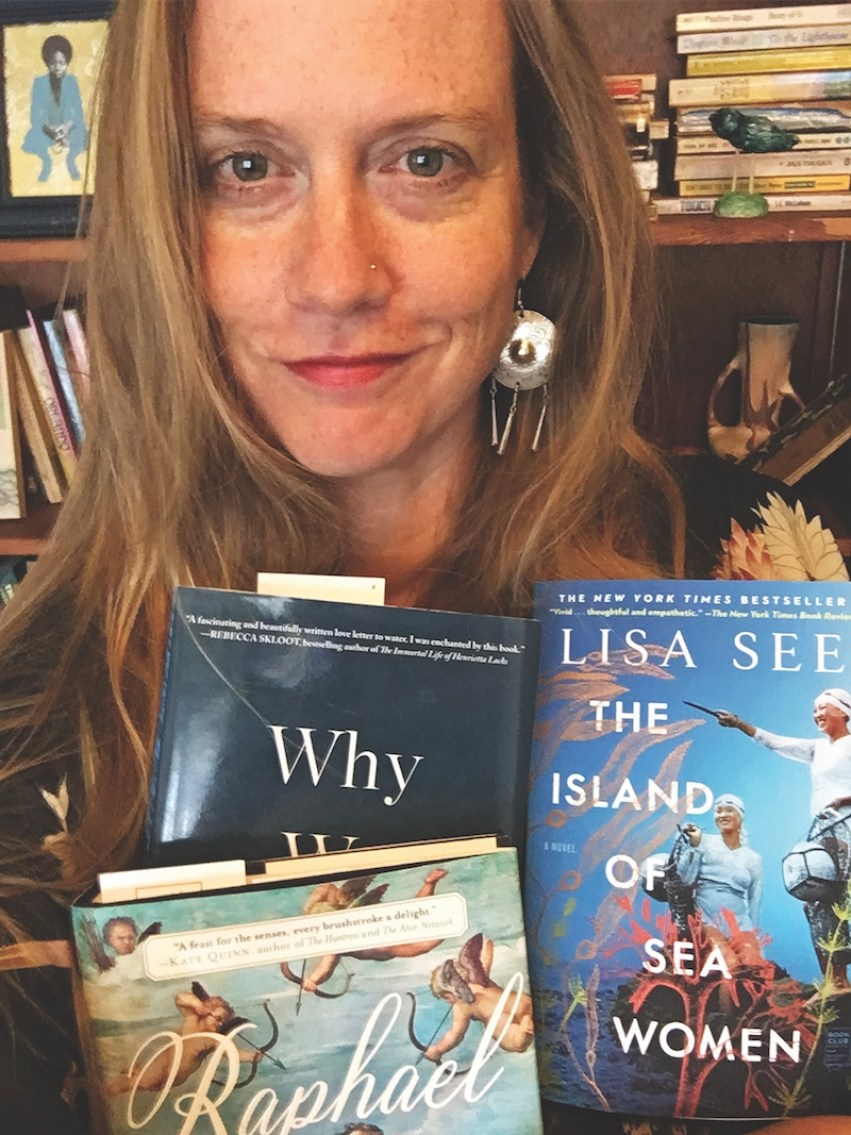Maureen McDole poses with three books