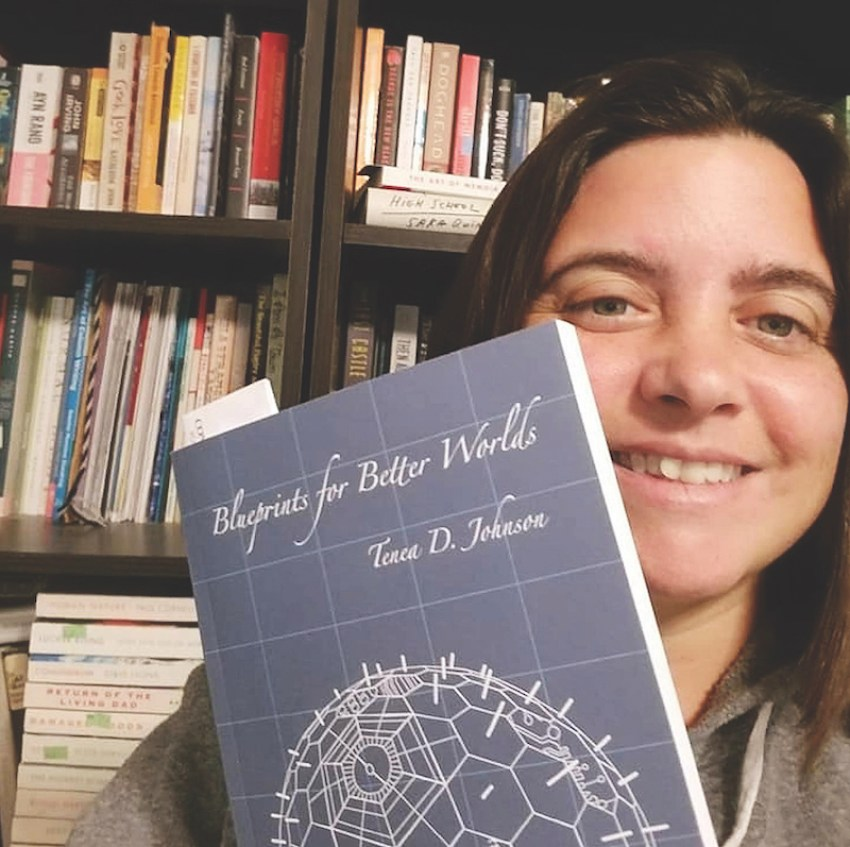 "Tiffany Razzano holds a copy of the book ""Blueprints for Better Worlds"""