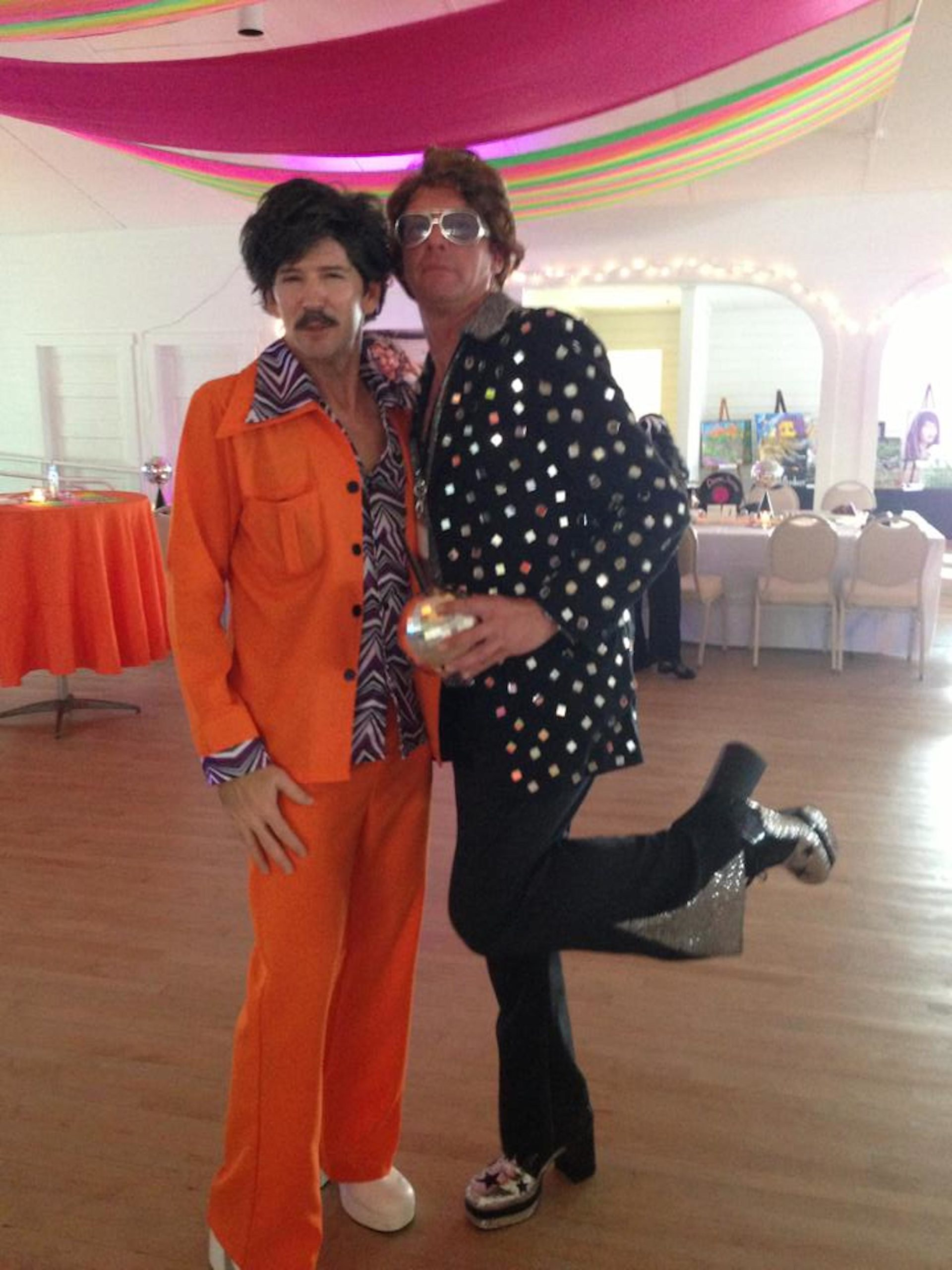 Two men in disco costumes, black and red, smile at camera.