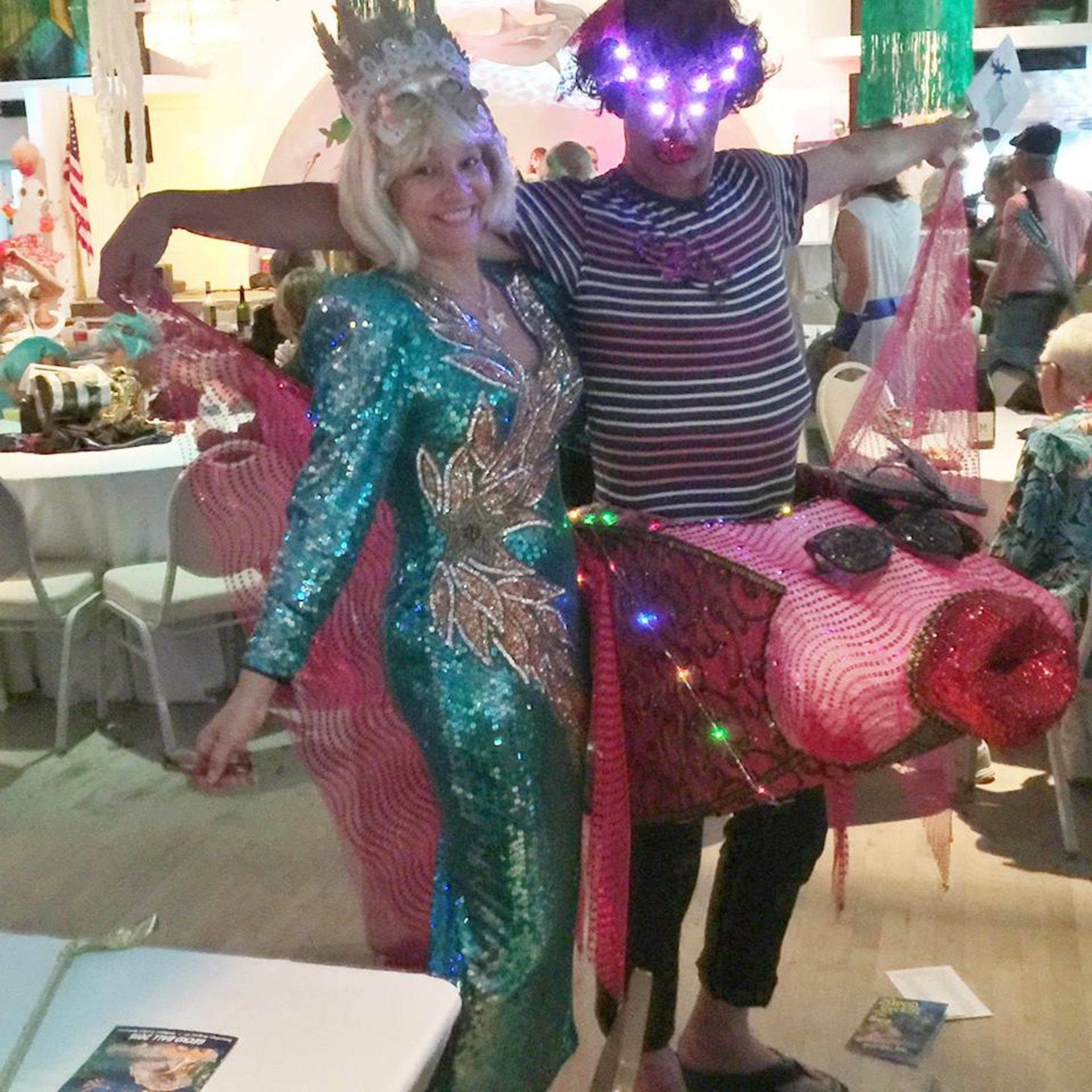 A woman in a mermaid costume and a man in a pink fish costume with lighted eyes smile at the camera.