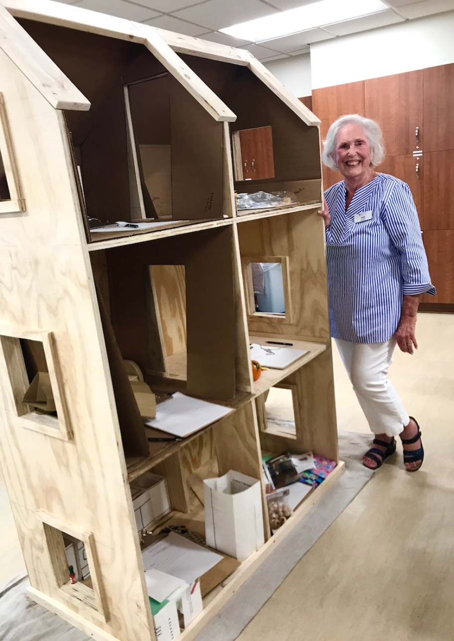 An older woman standing next to a three story dollhouse under construction.