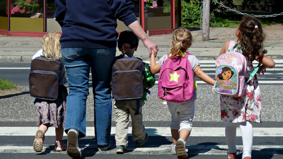 Children walking to school with multicolored backpacks and adult