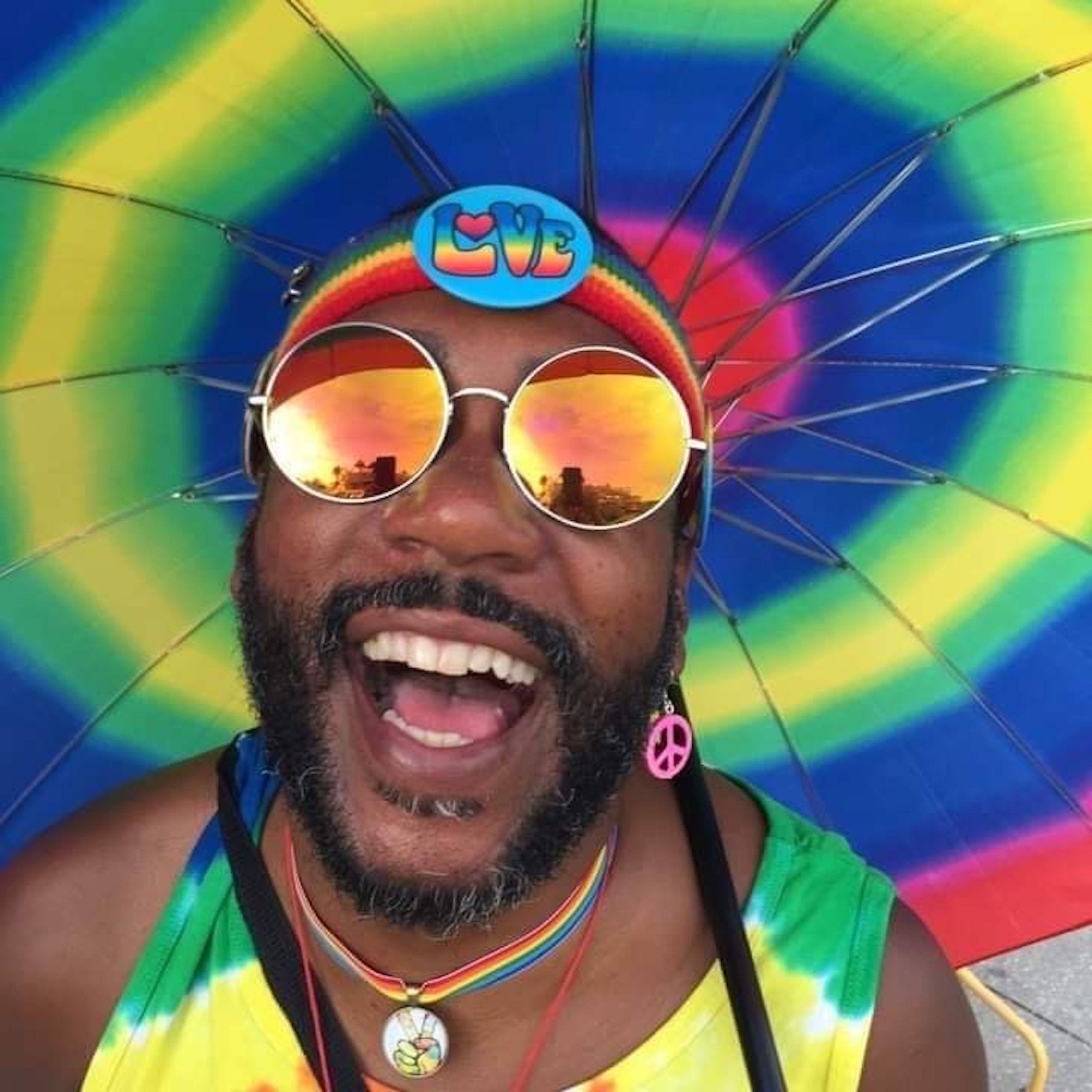 A man with a beard smiling and a rainbow umbrella background
