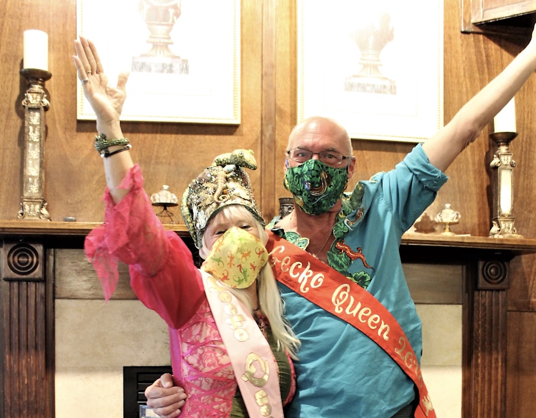 A man in a blue shirt and woman in a pink dress, both with face masks and sashes, pose with arms raised.