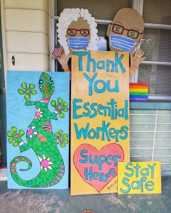 """""""Thank You Essential Workers, Stay Safe"""" painted on an artistic sign featuring a man, woman and green and pink gecko."""