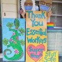 """Thank You Essential Workers, Stay Safe"" painted on an artistic sign featuring a man, woman and green and pink gecko."