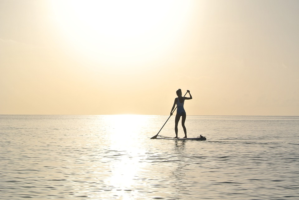 woman on paddleboard, setting sun in background