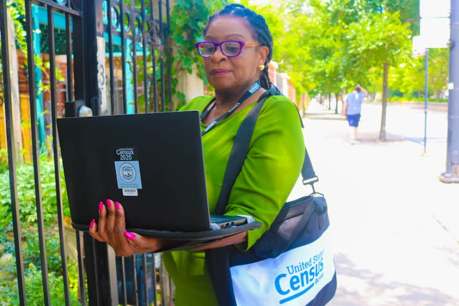 """A woman in a green shirt with a census bag and an open laptop with a sticker on it that reads """"U.S. Census 2020"""""""