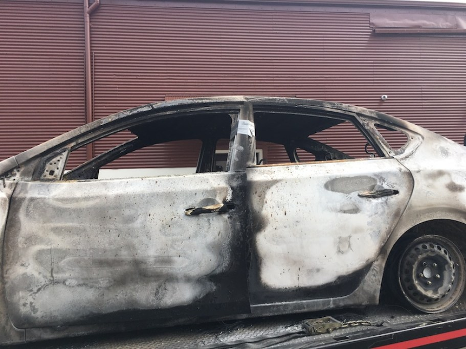 A white sedan with burn marks on it.