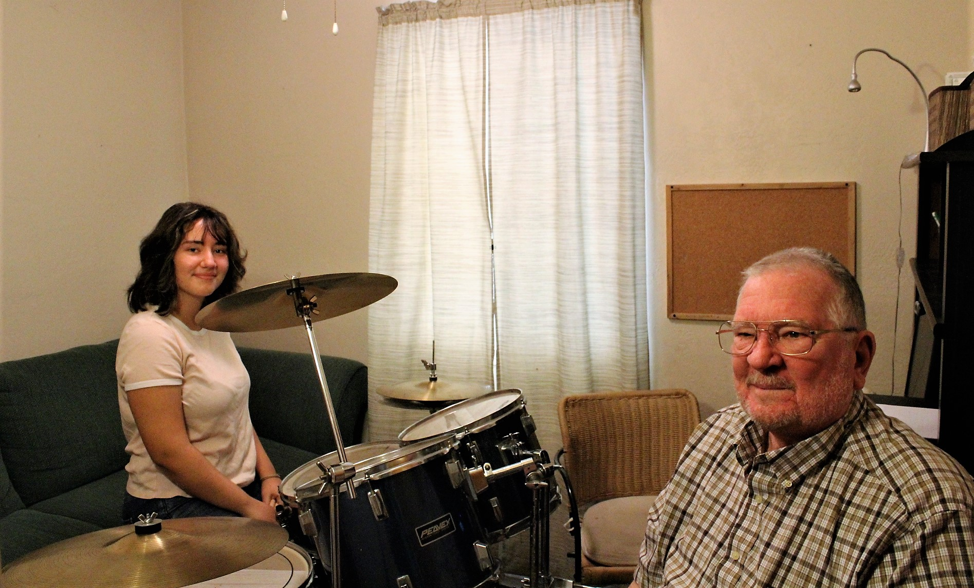 Arlene Assllani sits at her new drum set, donated by resident Donald Hensley, right.
