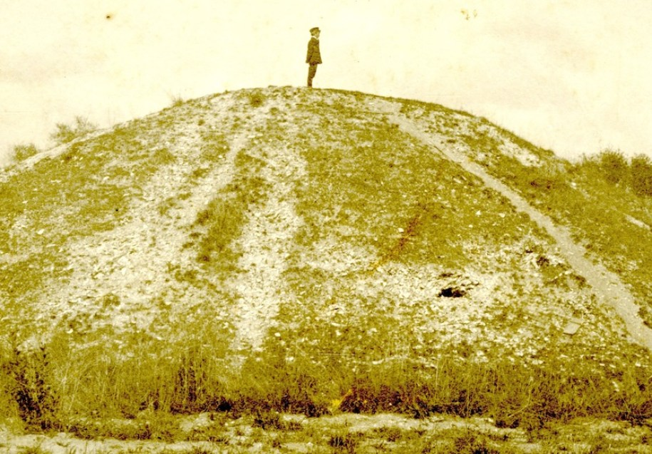 A sepia toned old photo of a man standing on an Indian burial mound.