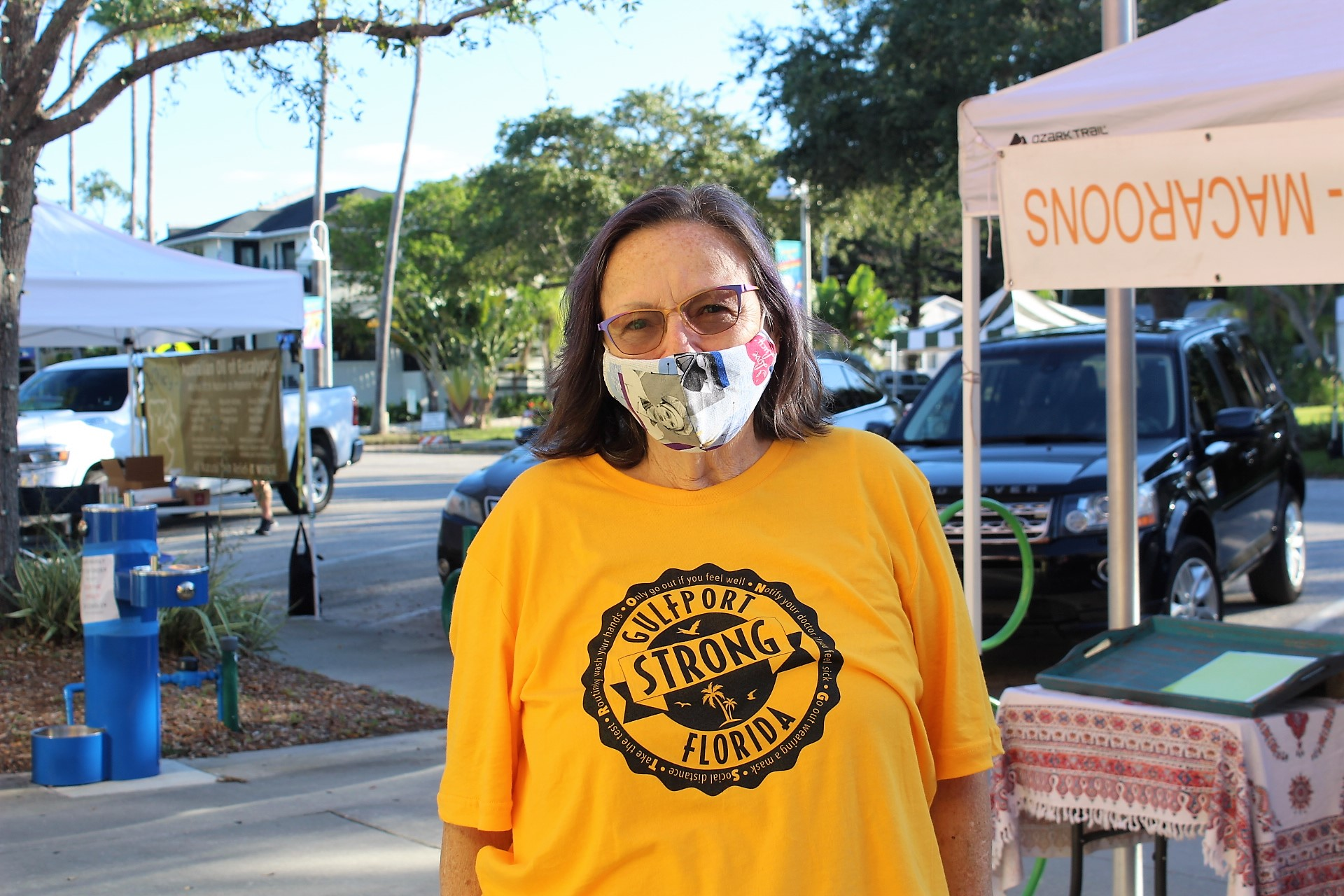 A woman in a gold t-shirt and face mask looks at the camera.