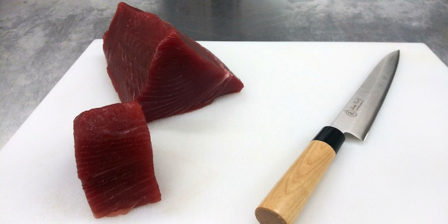 Large chunks of tuna cut on a white cutting board with knife.