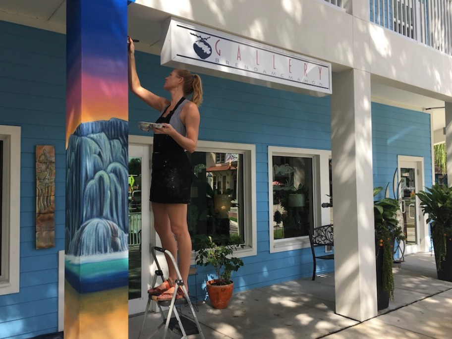A woman on a step ladder paints a mural on a column outside of an art gallery.