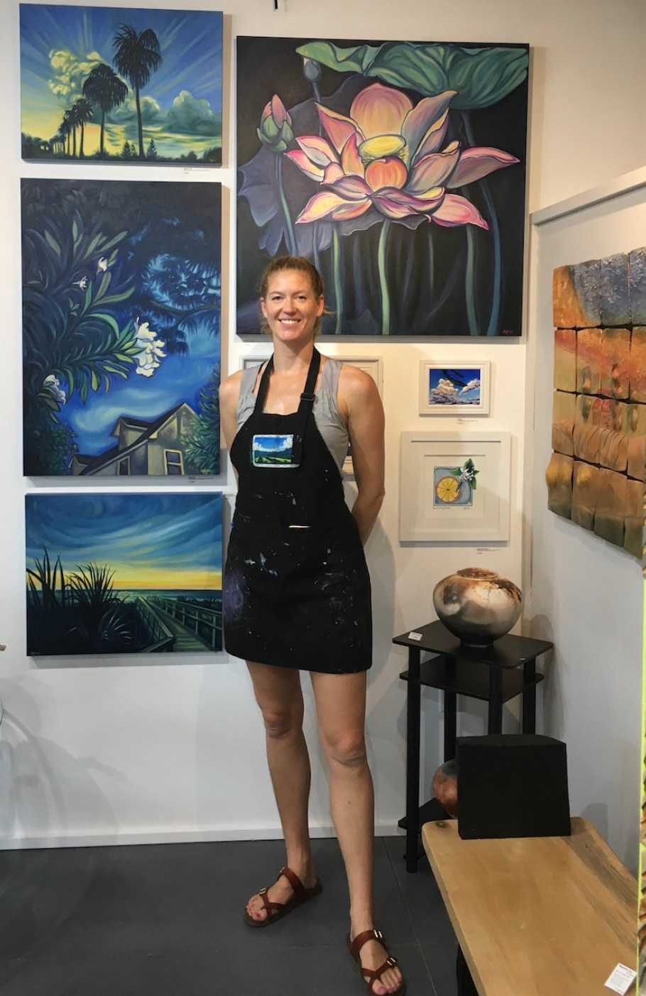 A woman in an apron stands in an art gallery surrounded by her work, smiling at the camera.