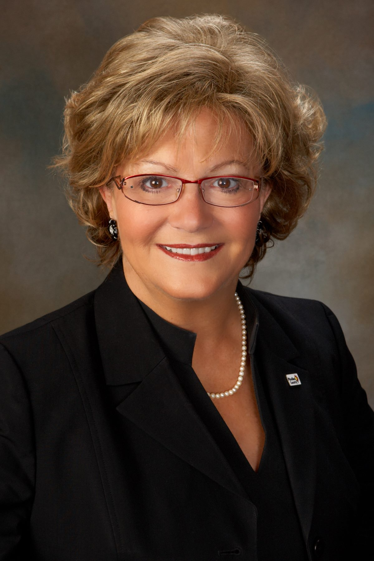 A head shot of a woman in glasses and a black suit.