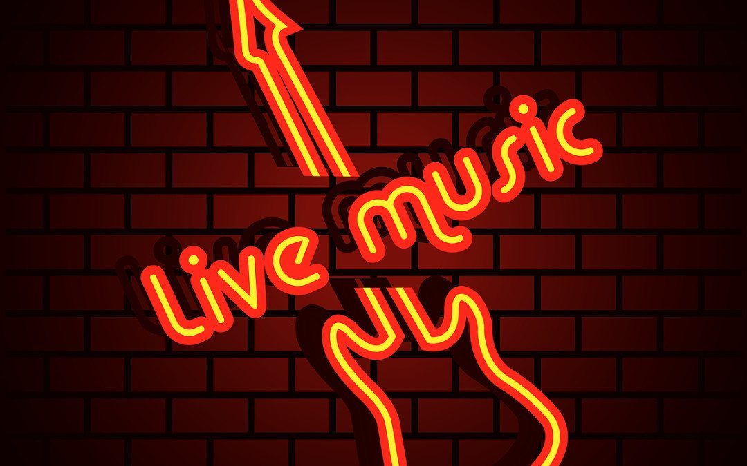 sign reading live music in red neon over shape of guitar