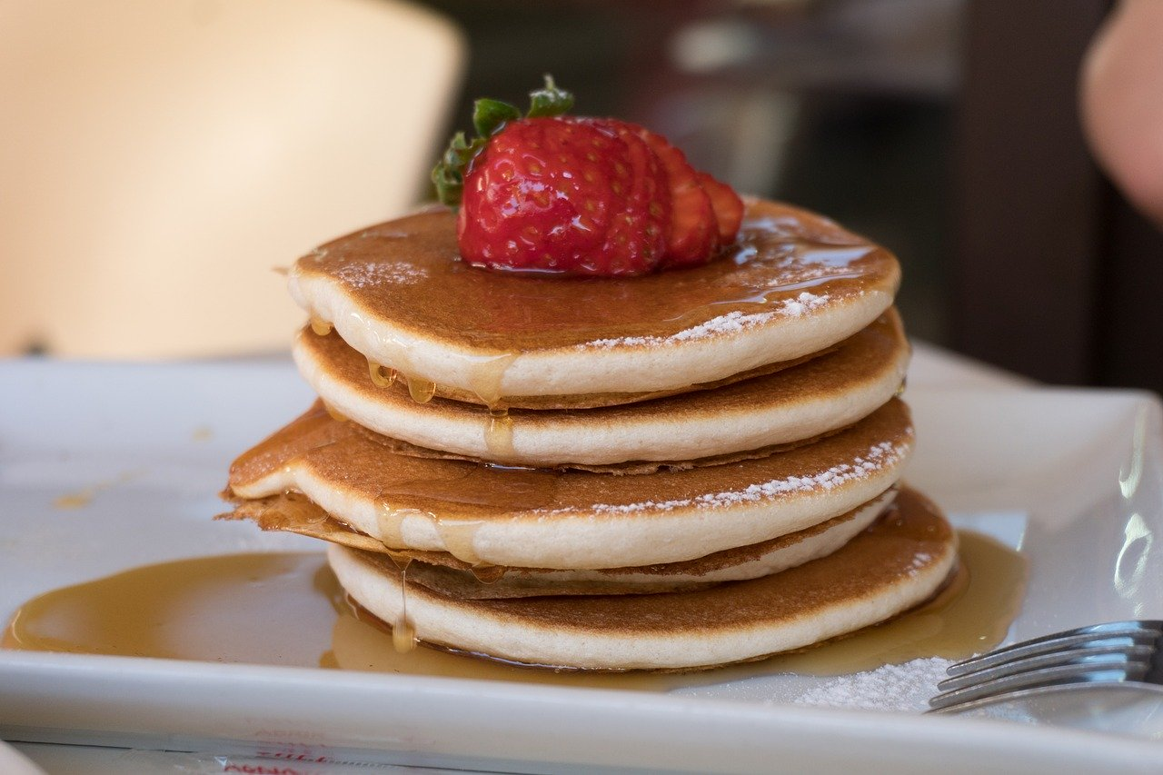 A stack of pancakes with syrup and strawberries on top.