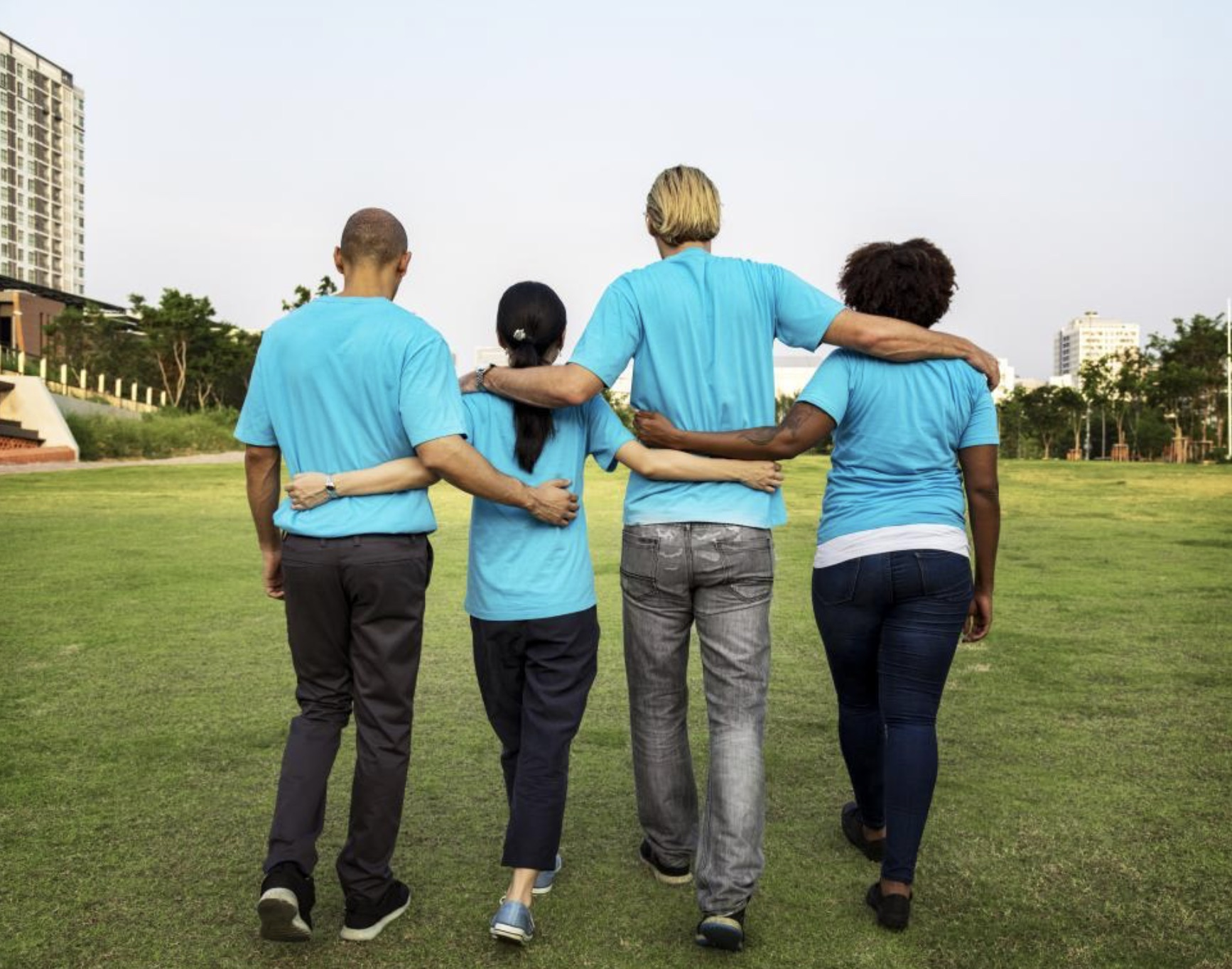 People with arms around each other wearing blue shirts in a field with backs to the camera.