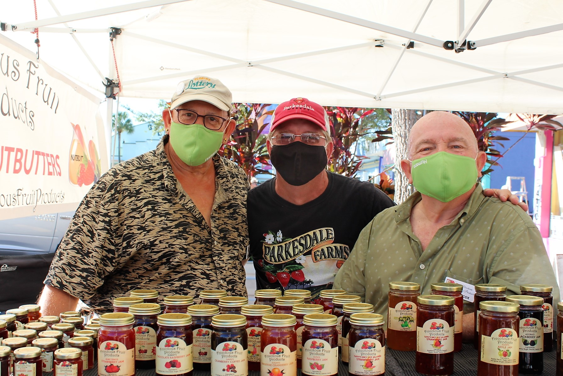 Three men in face masks in front of a display of jams, look at the camera.