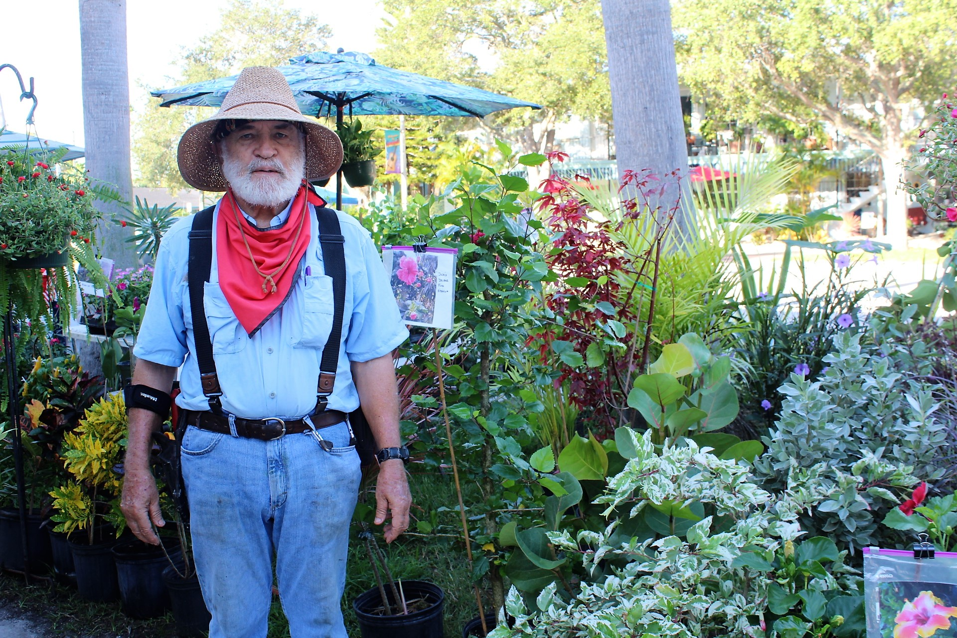 A man in a sun hat and red bandana stands in front of a garden.