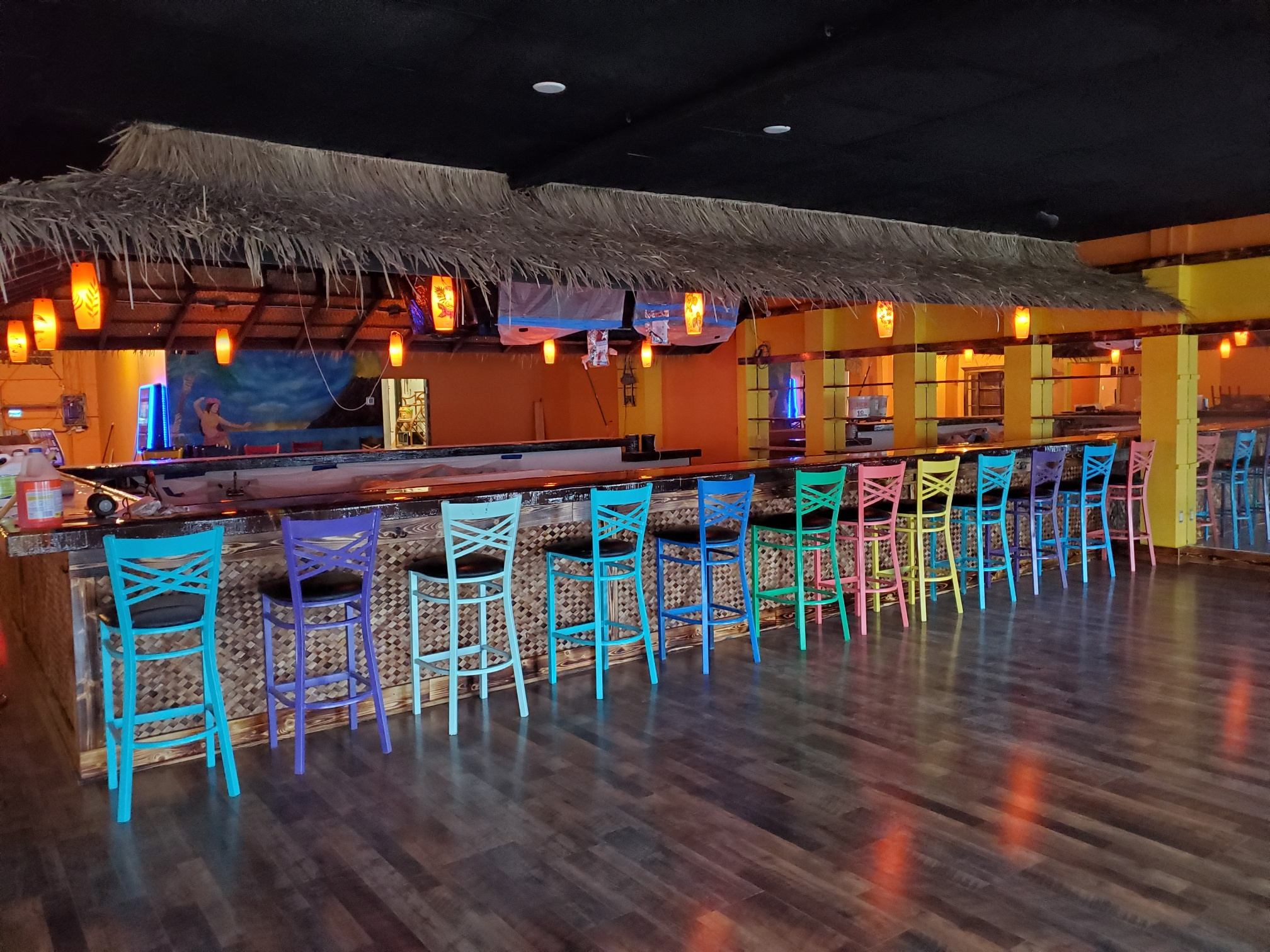 Indoor bar with thatched roof and multicolored bar chairs.