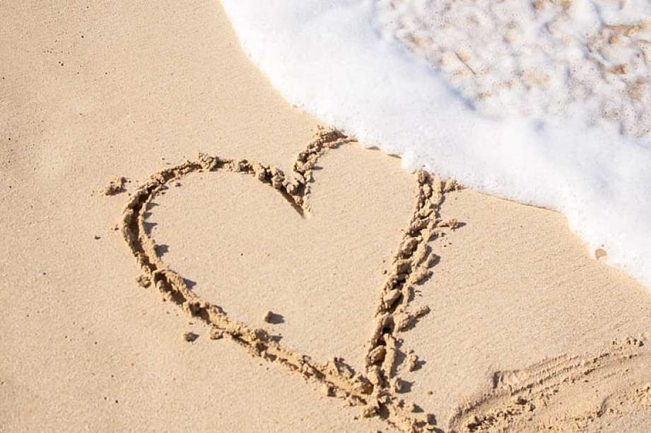A heart drawn in the sand with a wave crashing over it.