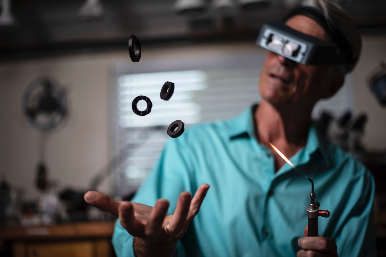 A man in a blue shirt and goggles catching three black rings.