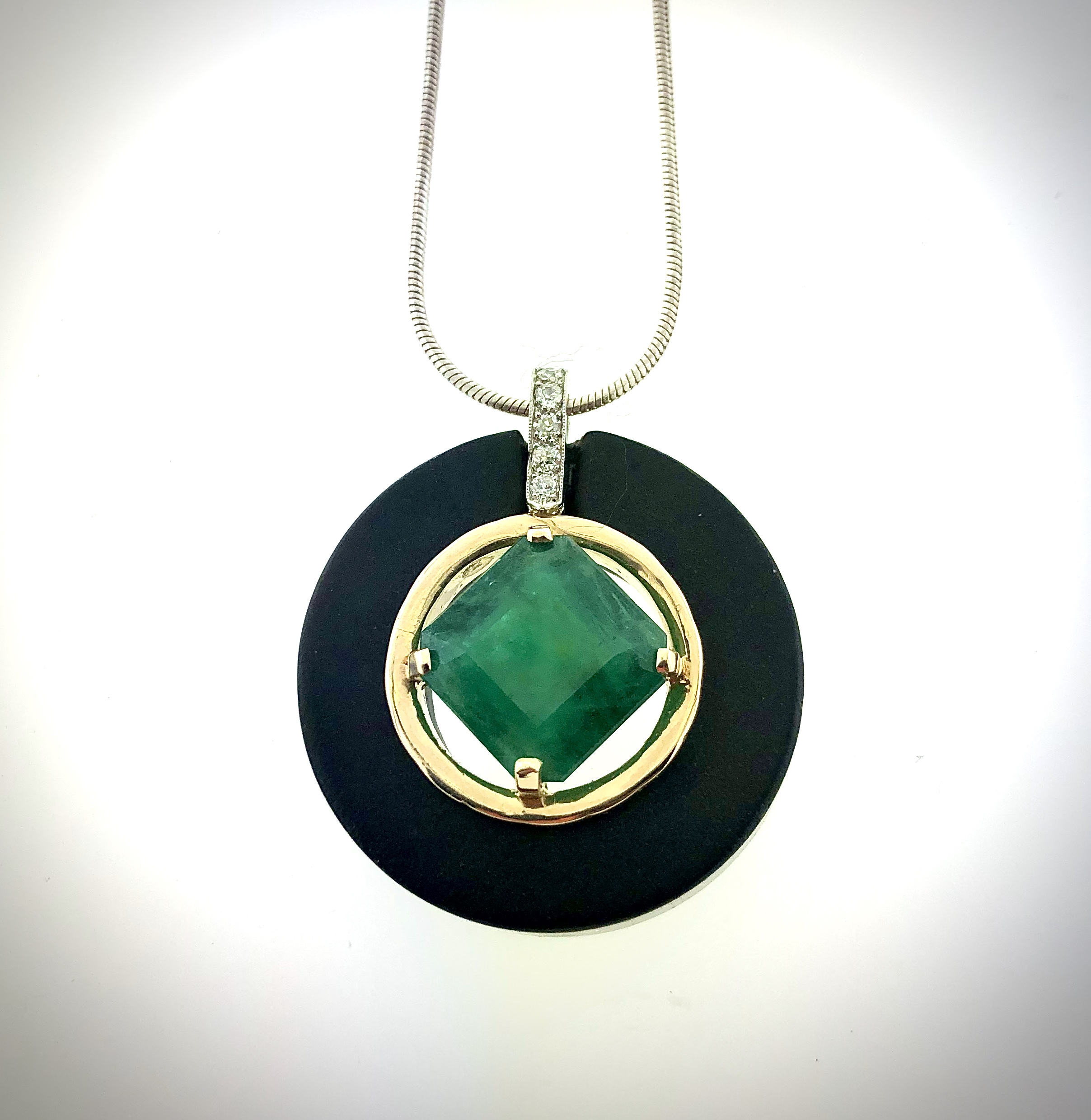 A green and black pendant of on a necklace