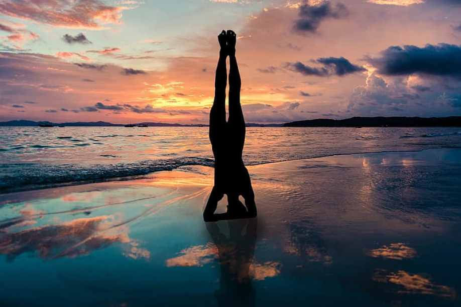A person on the beach at sunset doing a headstand near the water.