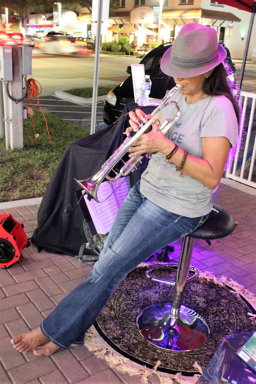 A woman in a fedora hat plays the trumpet while sitting on a stool wearing jeans and no shoes.