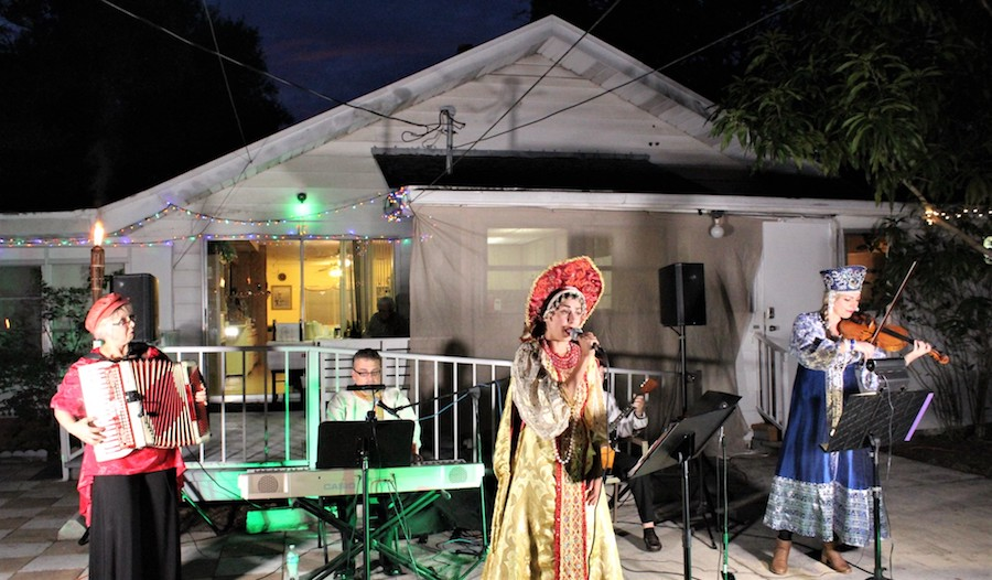 Three performers dressed in traditional Russian costumes sing and play outside of a house at night.