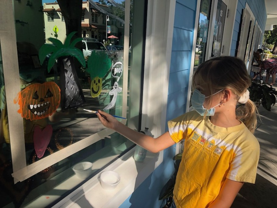 A girl in a yellow shirt and blue face mask paints a shop window with halloween decorations.