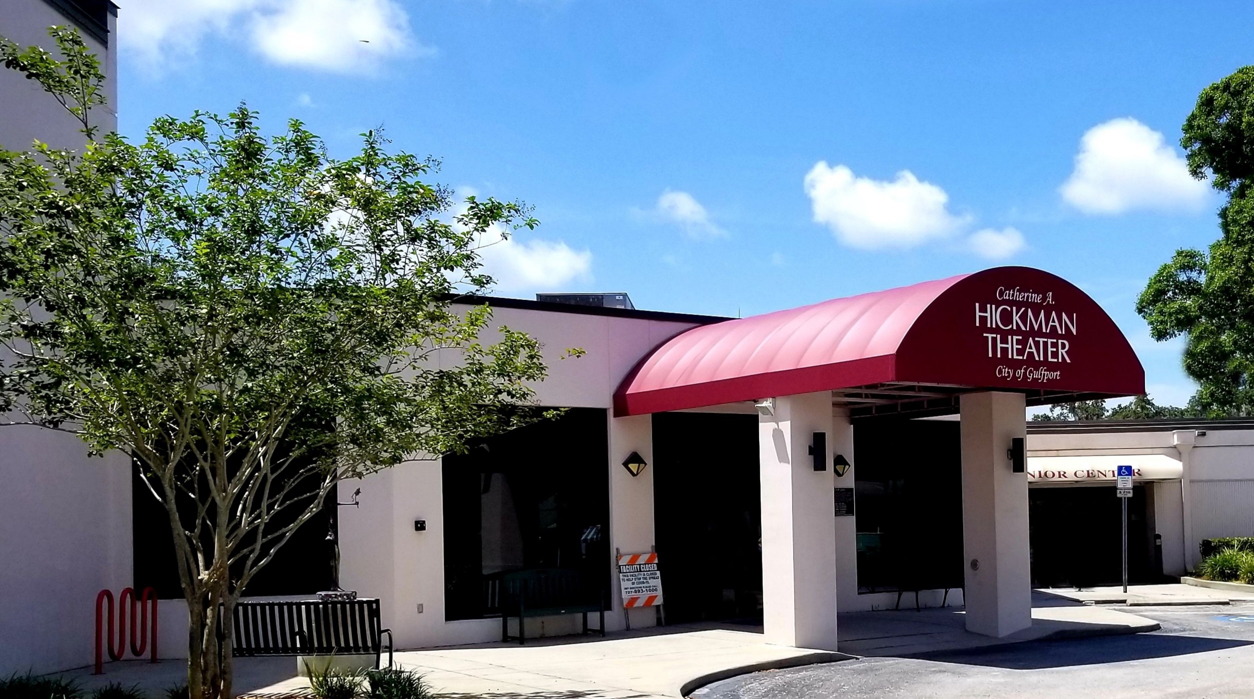 The entrance to the Catherine Hickman Theater in Gulfport Florida with maroon awning and blue sky.