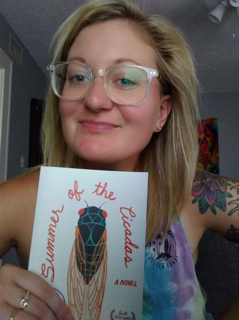A woman with glasses holding a book and smiling at the camera.
