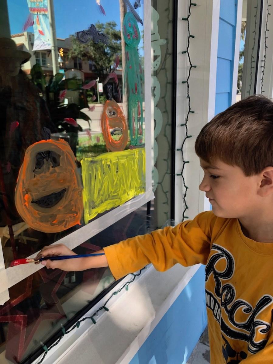 A boy in an orange shirt painting a scene on a shop window.