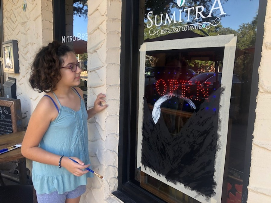 """A gril in a blue top looking at a shop window she is painting with the word """"Sumatra"""" written above it."""