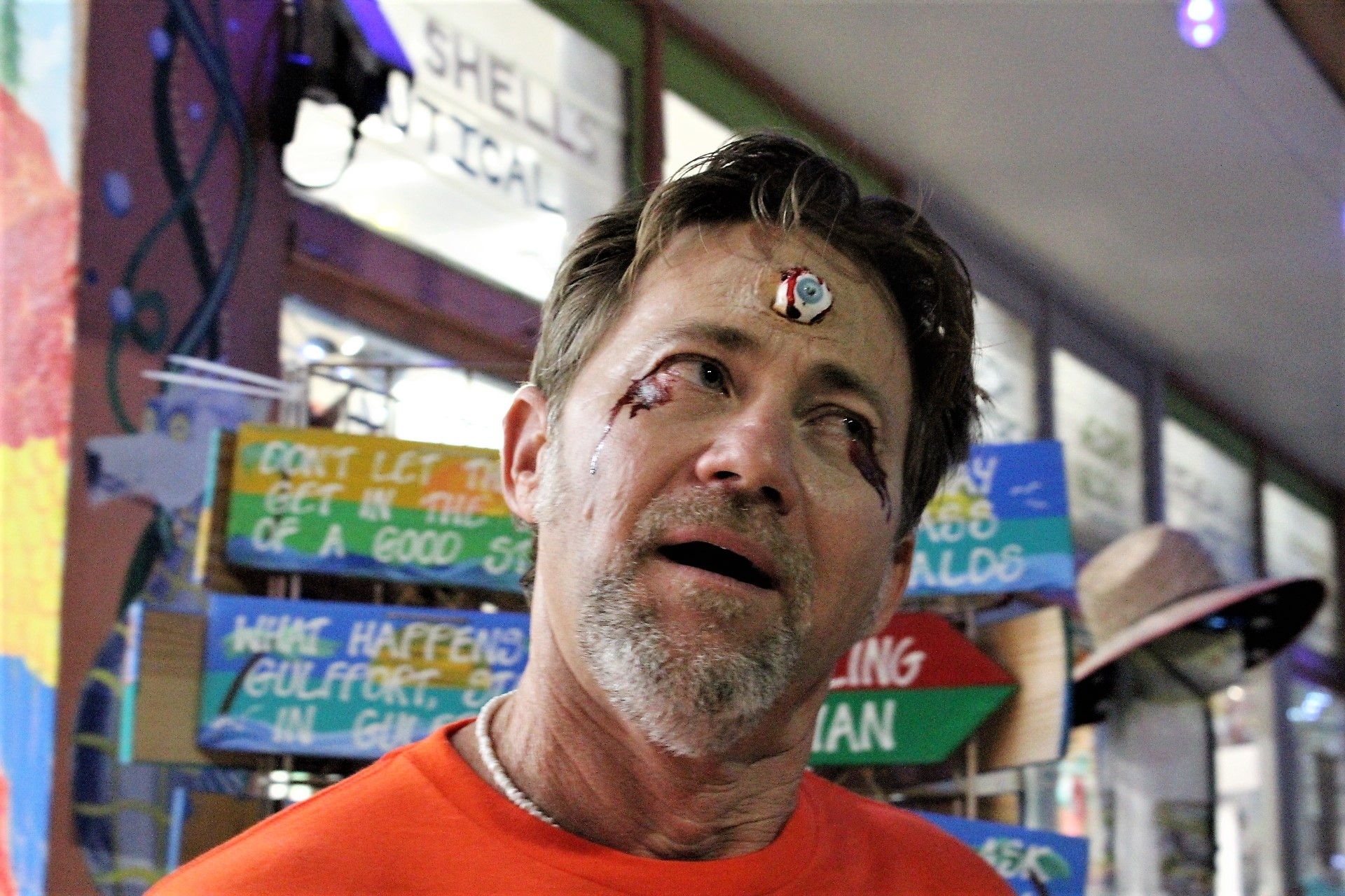 A man in an orange t-shirt with spooky face paint.