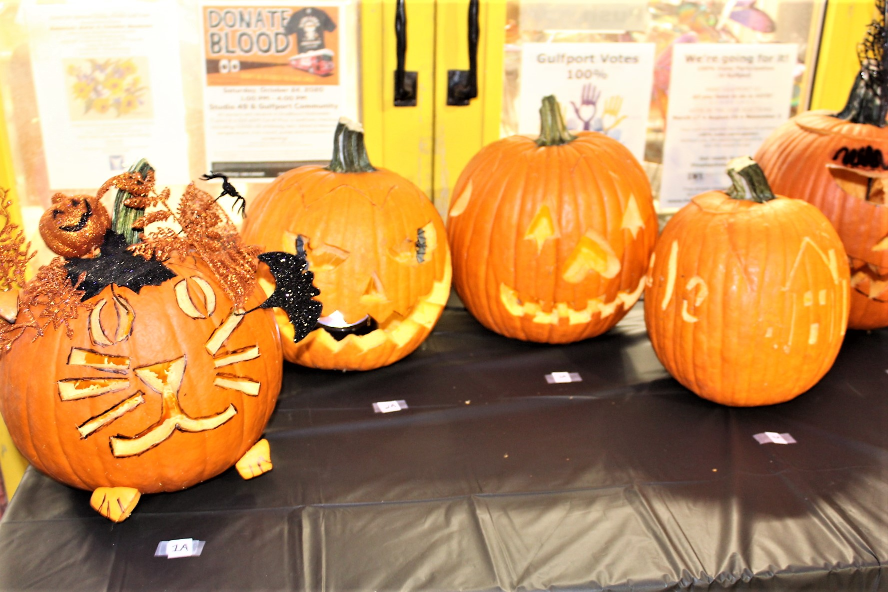 A group of orange, carved and decorated Halloween pumpkins.