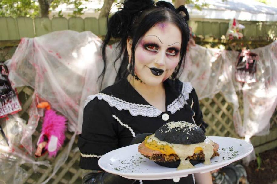 A woman in gothic makeup and black dress holds a black bun sandwich.