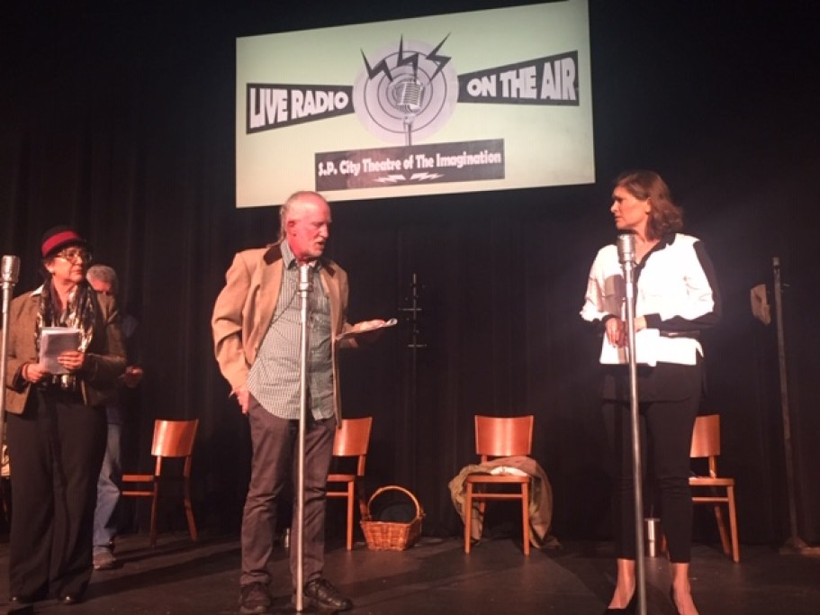 A stage with two actors distanced and speaking into microphones.