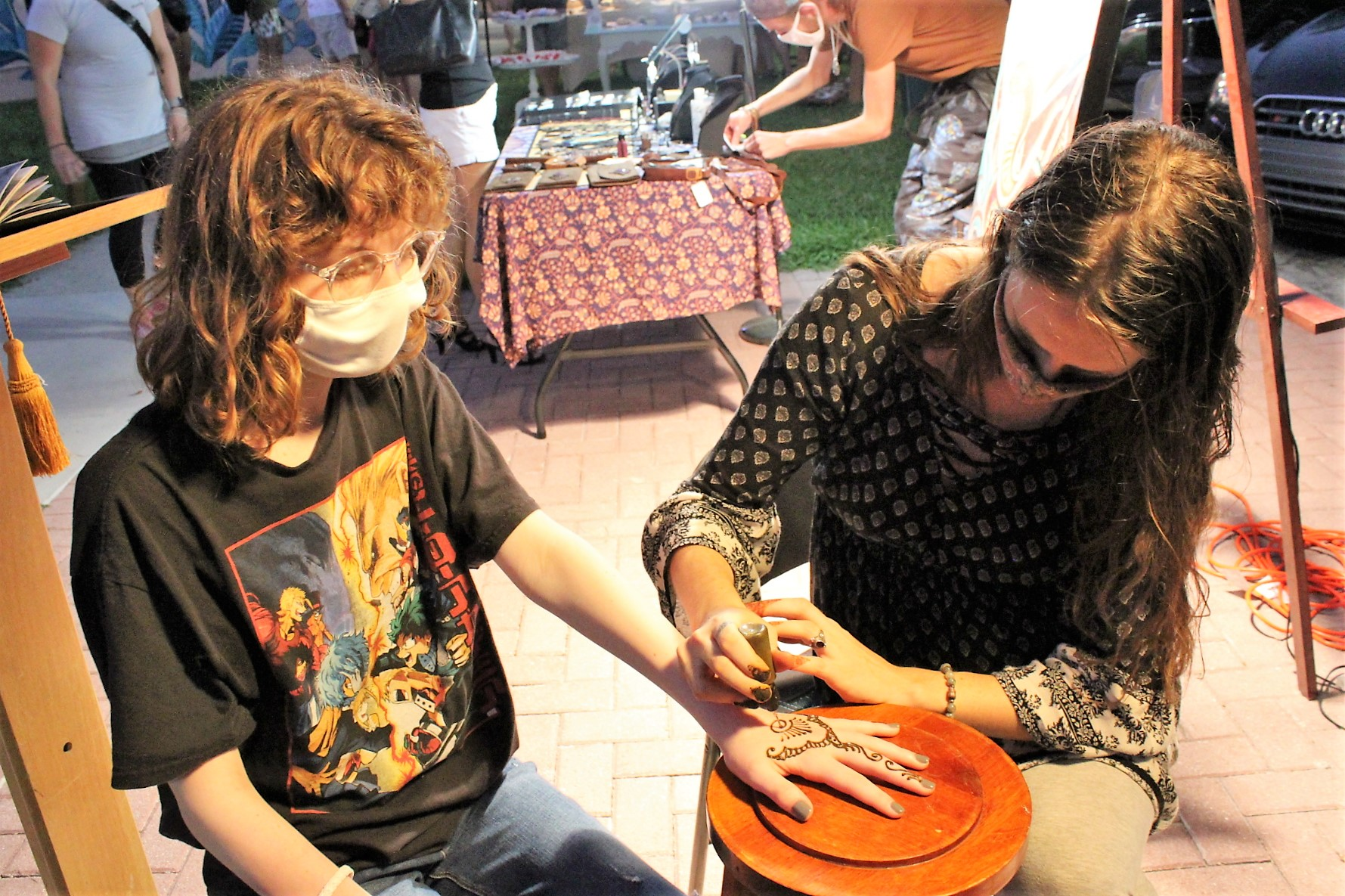 Two people sit at a henna painting station as one paints another's hand with henna.