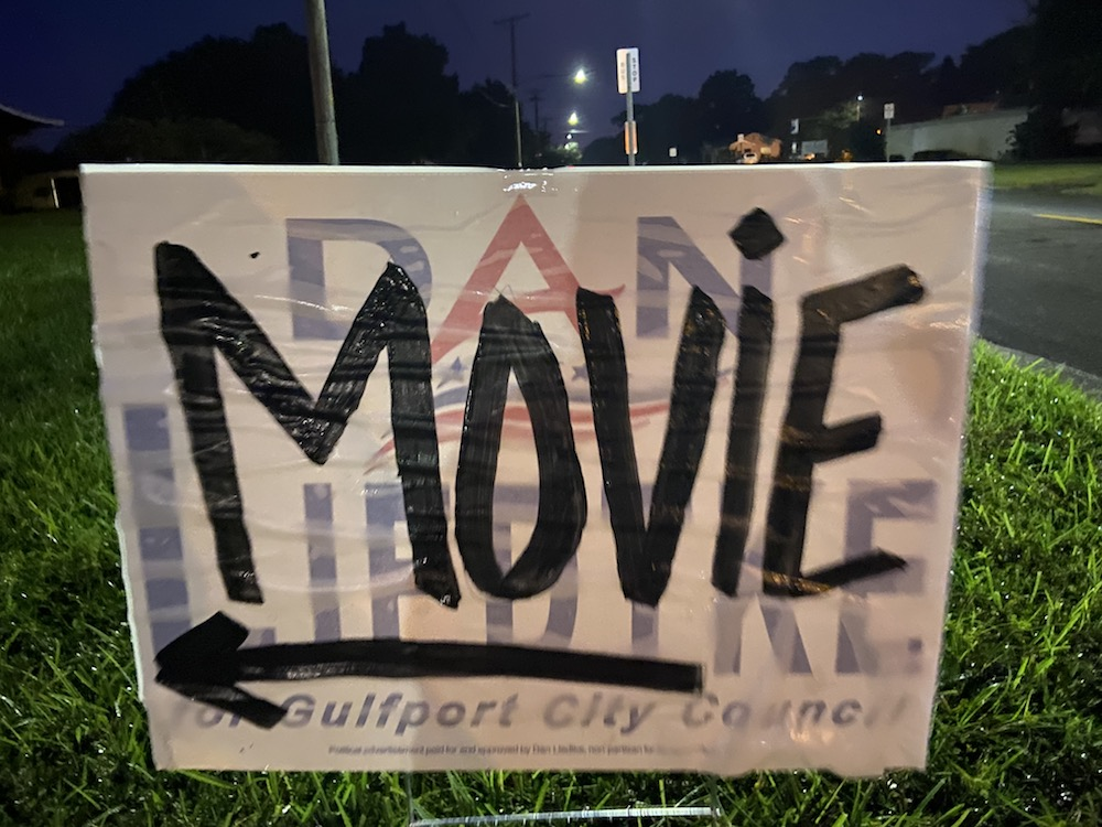 "A sign that reads ""Movie"" over an old campaign poster."