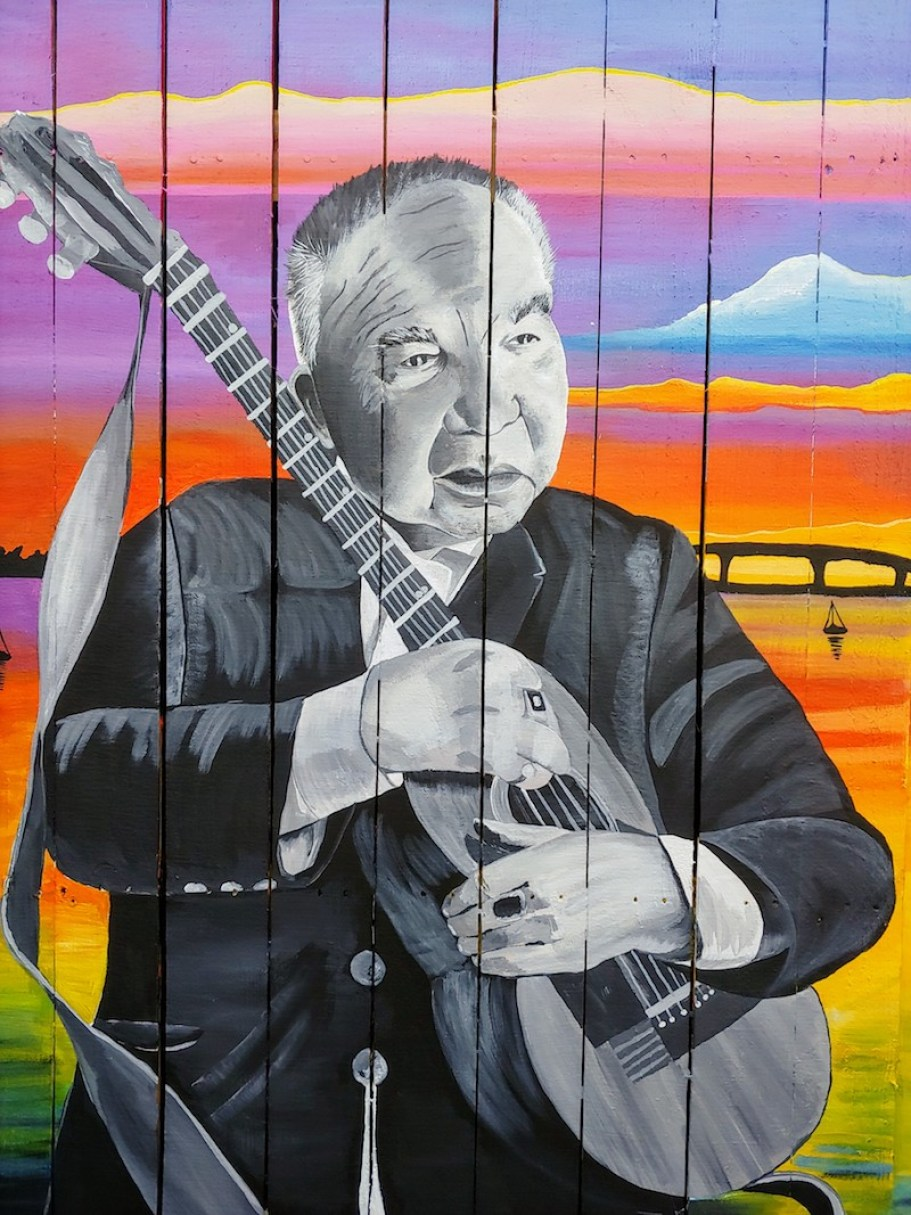 A close-up colorful portrait of John Print holding a guitar